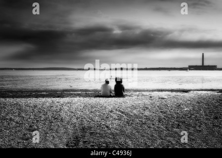 people sitting on a pebble beach at low tide at southampton water UK black & white - Stock Photo