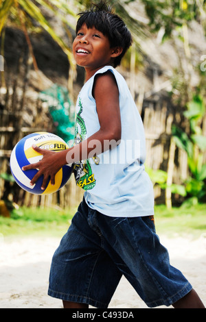 Portrait of a young Kuna boy playing volleyball in his back yard on Nalunega island in the San Blas archipelago, - Stock Photo