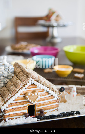 Gingerbread log cabin house being decorated - Stock Photo