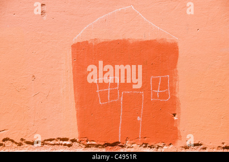 A simple house illustration made with paint and chalk on an outside orange wall. - Stock Photo