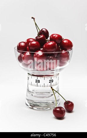 Cherries in Glass Dish and Tape Measure in Inches - Stock Photo