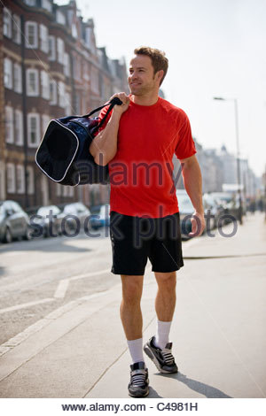 A young man carrying a sports bag, walking down the street - Stock Photo