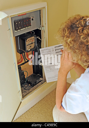Woman contemplating the rising energy prices and bills in the UK as she reads her electricity meter - Stock Photo