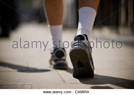 A close-up of a young man jogging in trainers, rear view - Stock Photo