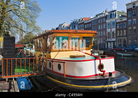 Houseboat on Prinsengracht with the tower of the Westerkerk behind, Grachtengordel, Amsterdam, Netherlands - Stock Photo