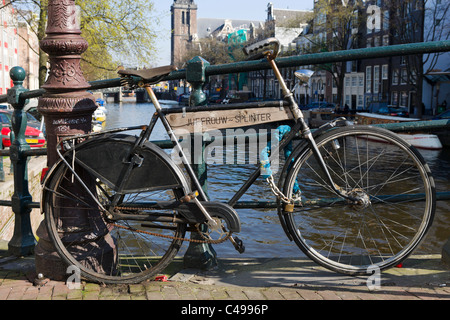 Bicycle on a bridge over Prinsengracht canal with the Westerkerk behind, Grachtengordel, Amsterdam, Netherlands - Stock Photo