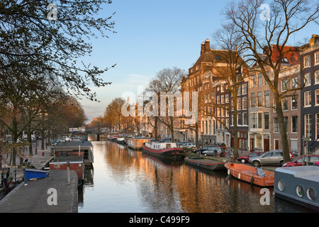 Houses and houseboats on a canal in early spring/late winter, Prinsengracht, Grachtengordel south, Amsterdam, Netherlands - Stock Photo