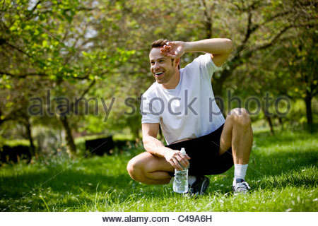 A young man taking a rest from running, holding a bottle of water - Stock Photo