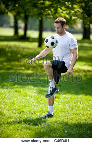 A young man playing with a football - Stock Photo