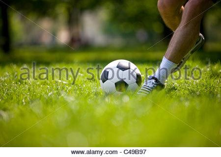 A young man kicking a football outdoors - Stock Photo