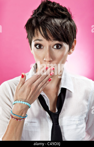A young woman with funky short brown hair covering her mouth, wearing a button down shirt and necktie. - Stock Photo