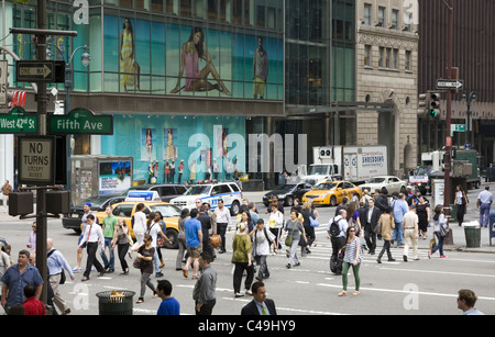 The always busy street corner of 5th Avenue and 42nd Street in New York City. - Stock Photo