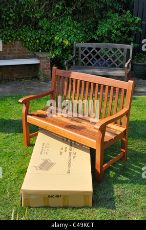 Imported self assembly hardwood garden seat and empty box with import markings - Stock Photo