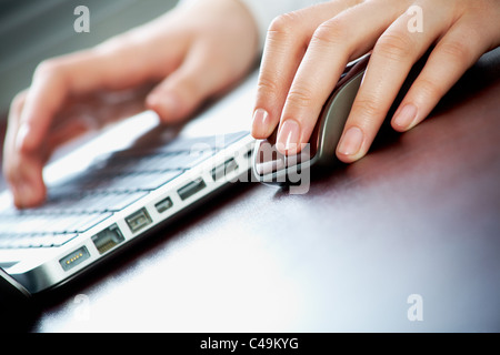 Close-up of female hand on mouse during computer work - Stock Photo