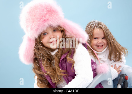 Happy girl in pink furry hat looking at camera with her sister on background - Stock Photo