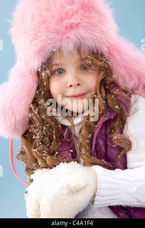Happy girl in pink furry hat with snow in hands looking at camera - Stock Photo