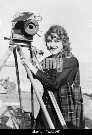 Vintage photo circa 1916 of Canadian-born film actress Mary Pickford (1892 - 1979) standing next to a motion picture - Stock Photo
