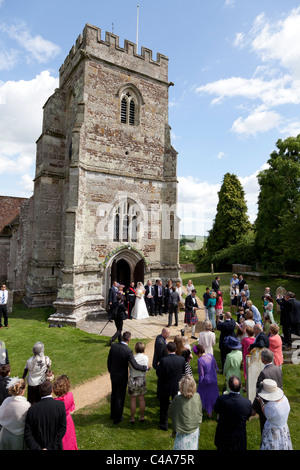 wedding guests and family watching bride and groom outside St Mary & Cuthberga & All Saints Church Witchampton - Stock Photo