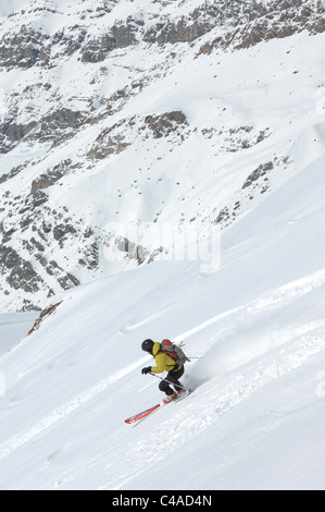A man skiing wearing a rucksack off piste in fresh snow under a blue sky in Dizin resort part of the Alborz mountains - Stock Photo