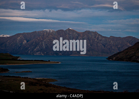 Lake Hawea at dusk seen from the neck, with Southern Alps in the background, New Zealand - Stock Photo