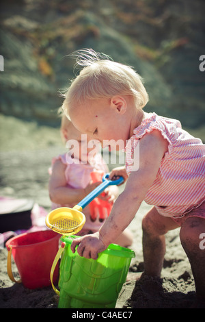 1 Year Old Twin Girls Playing With Sand Toys at the Beach - Stock Photo