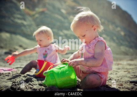 Identical Twin 1 Year Old Girls Playing with Sand Toys at the Beach - Stock Photo