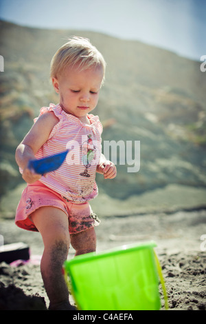 I Year Old Girl at Beach Playing with Sand Toys - Stock Photo
