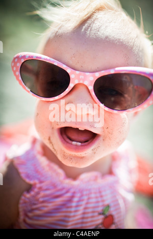 Toddler Girl Wearing Big Sunglasses at the Beach - Stock Photo