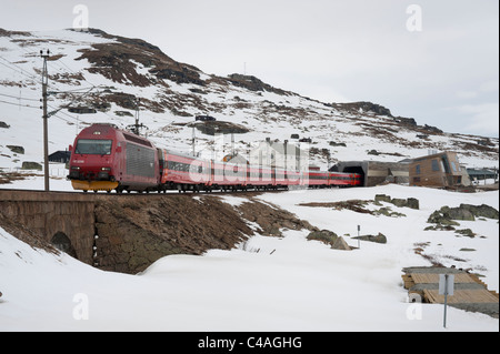 Electric train leaves Finse station for Bergen, southern Norway. - Stock Photo