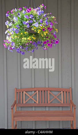 A full and vivid hanging flower pot of colorful petunias hangs above an empty wooden bench on the streets of Jackson - Stock Photo