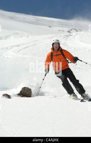 A man skiing wearing a helmet off piste in fresh snow under a blue sky in Dizin resort part of the Alborz mountains - Stock Photo