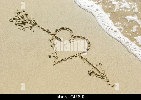 Heart pierced by Cupid's arrow drawn in the sand - Stock Photo