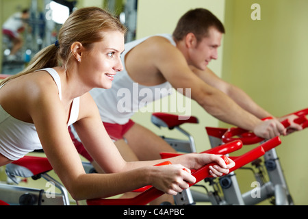 Portrait of sporty couple doing physical exercise on special equipment - Stock Photo