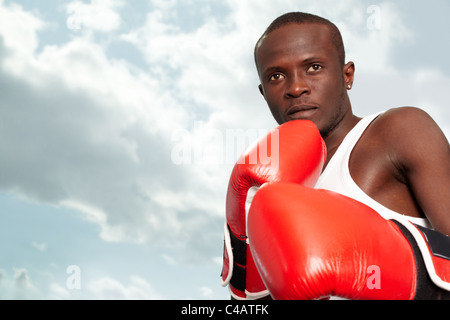 Image of a boxer in red gloves against cloudy sky - Stock Photo