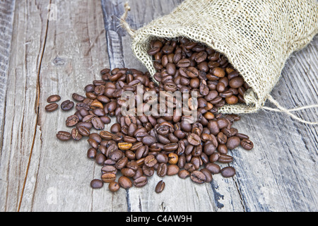 Coffee beans in a jute bag on a wooden table - Stock Photo
