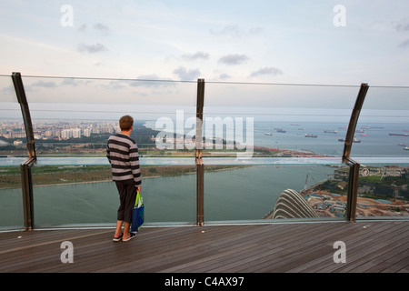 Singapore, Singapore, Marina Bay. A man looks out over city from observation deck of Marina Bay Sands SkyPark. - Stock Photo