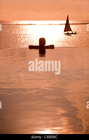 Zanzibar, Matemwe Bungalows. A tourist stands at the edge of an infinity pool watching the Dhows. MR. - Stock Photo
