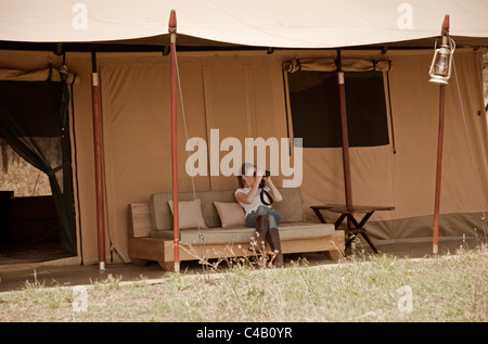 Tanzania, Serengeti. A guest looks out over the plains from the comfort of her tent at Lemala Ewanjan. MR. - Stock Photo