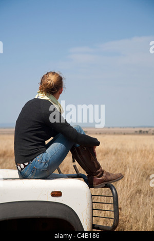 Tanzania, Serengeti. A woman looks out over the Serengeti plains from the bonnet of her Land Rover. MR. - Stock Photo