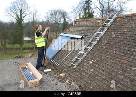 Engineers installing solar thermal evacuated tube array on the roof of a domestic house to provide renewable heat - Stock Photo