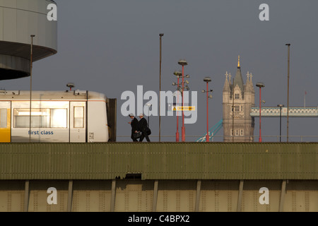london commuters walk to first class train on London Cannon Street station Railway Bridge, with Tower Bridge in - Stock Photo