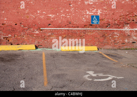 Handicapped/Disabled parking space in the USA against a brick wall in a parking lot. - Stock Photo