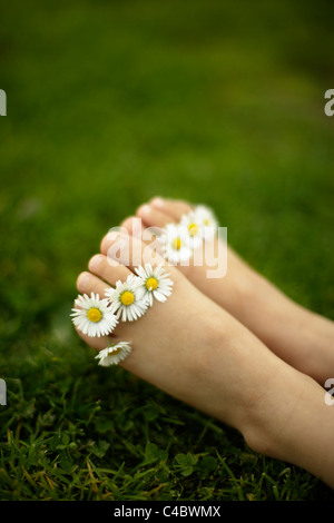 Five year old girl with daisies between her toes - Stock Photo