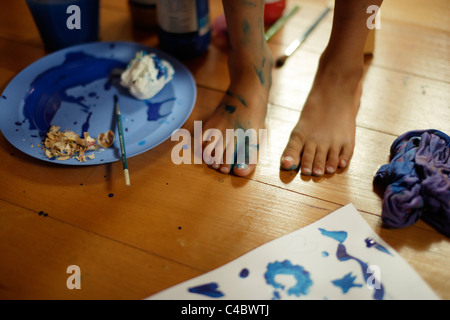 Young girl makes a mess painting in her room. - Stock Photo