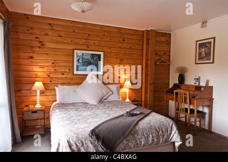 Nice warm bedroom interior of mountain lodge. Fox Glacier Lodge, Fox Glacier, West Coast, South Island, New Zealand. - Stock Photo