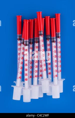 Many insulin syringes on blue - Stock Photo