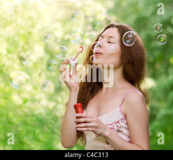 Young beautiful girl blowing bubbles in the park on green background - Stock Photo