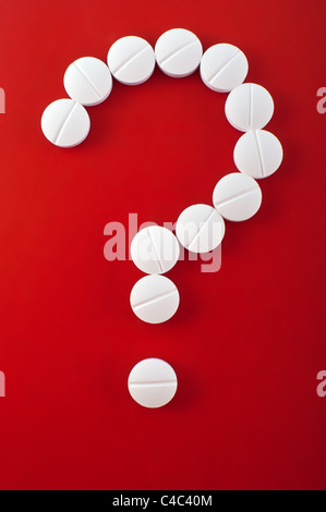 White tablets on red background as question mark - Stock Photo