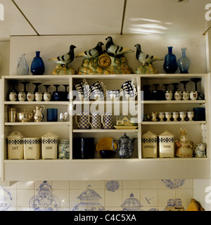 Assorted country style crockery in kitchen shelving - Stock Photo