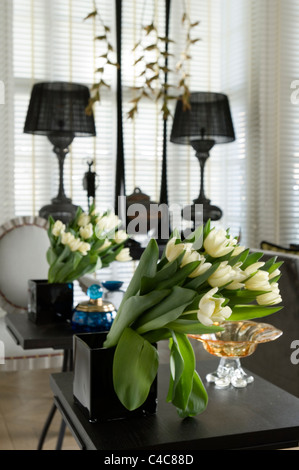 Bunch of tulips in a black square vase with mirror reflection - Stock Photo